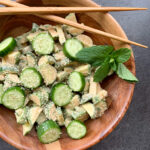 A wooden bowl of Tahini Lime Cucumber Salad with two chopsticks