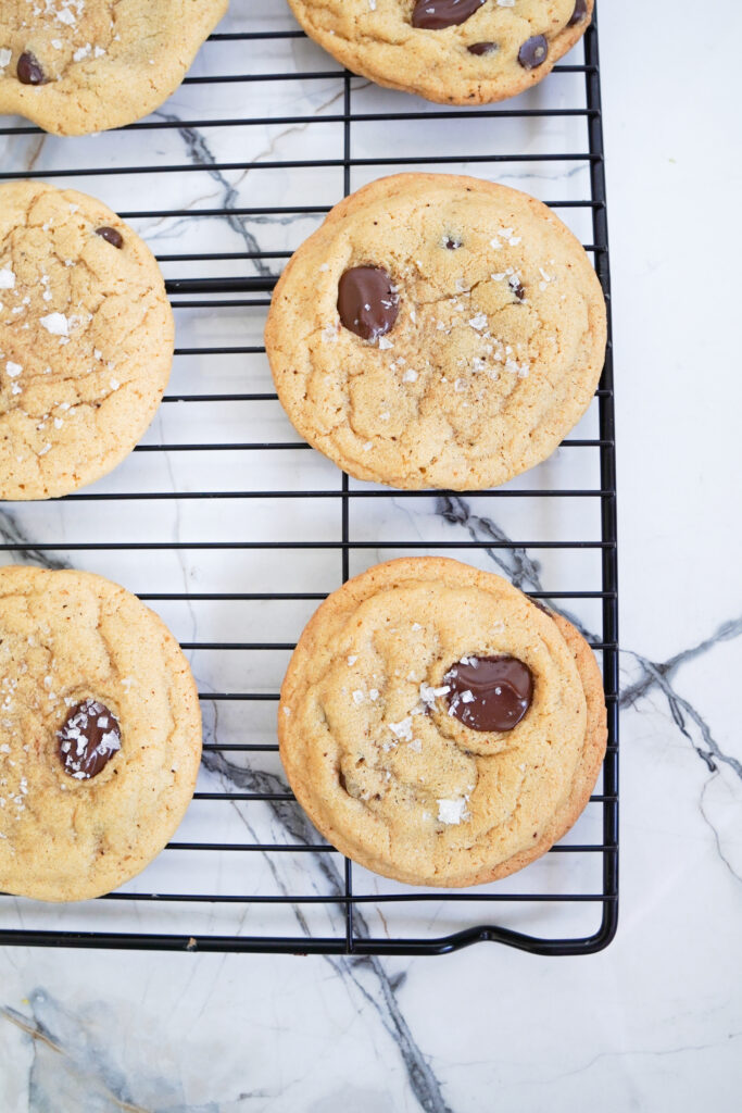 Six baked Brown Buttered Chocolate Chip Cookes on a black cooling rack