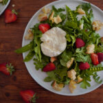 A large white plate with Strawberry Burrata Salad with Hand Torn Croutons on a wooden table.