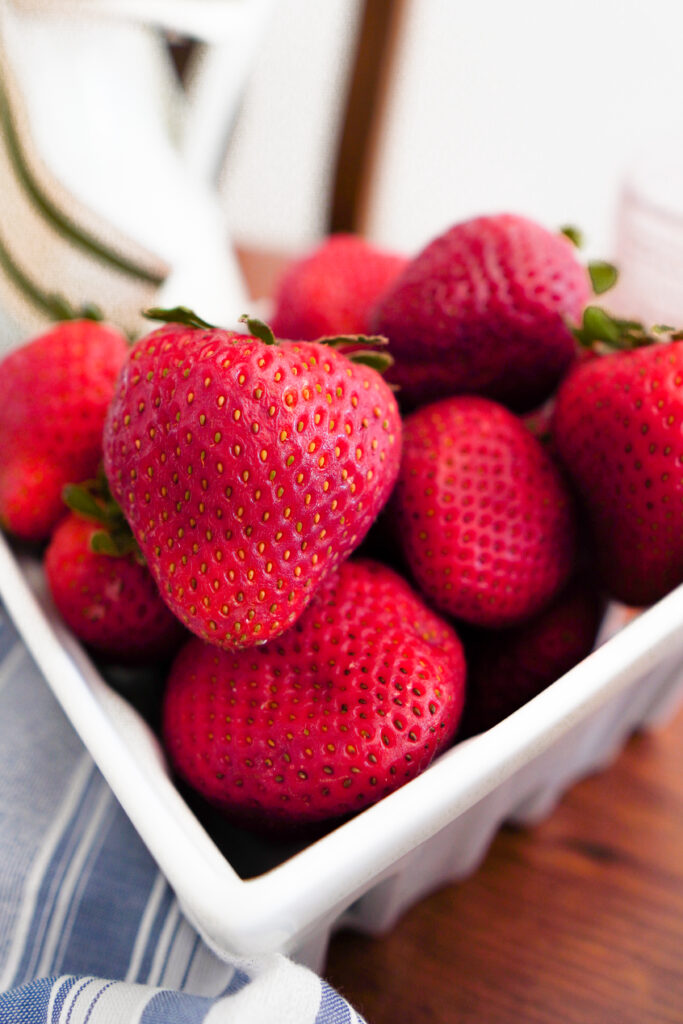 White glass crate full of large red strawberries