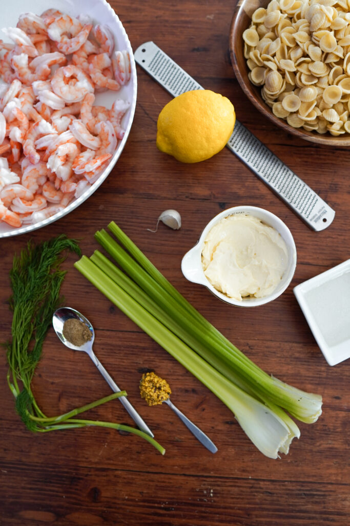 A white bowl full of shrimp surrounded by celery, a lemon, one clove of garlic, dill, pasta, a spoon full of salt, and a spoon full of mustard