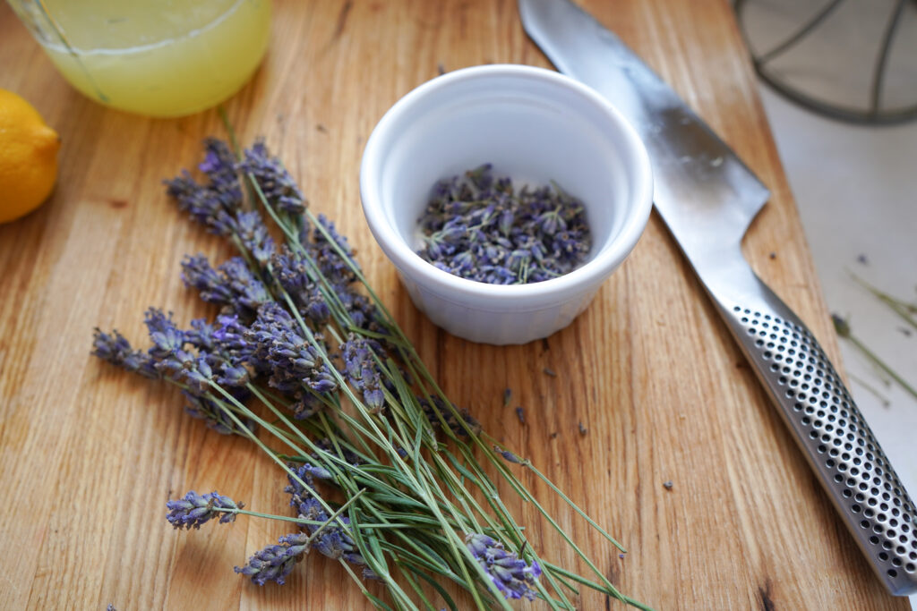 On a wood cutting board lays fresh cut lavender, a white bowl and a knife