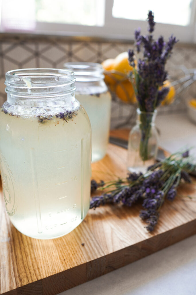 Two mason Jars with the lid off full of lavender lemonade with the lavender buds floating