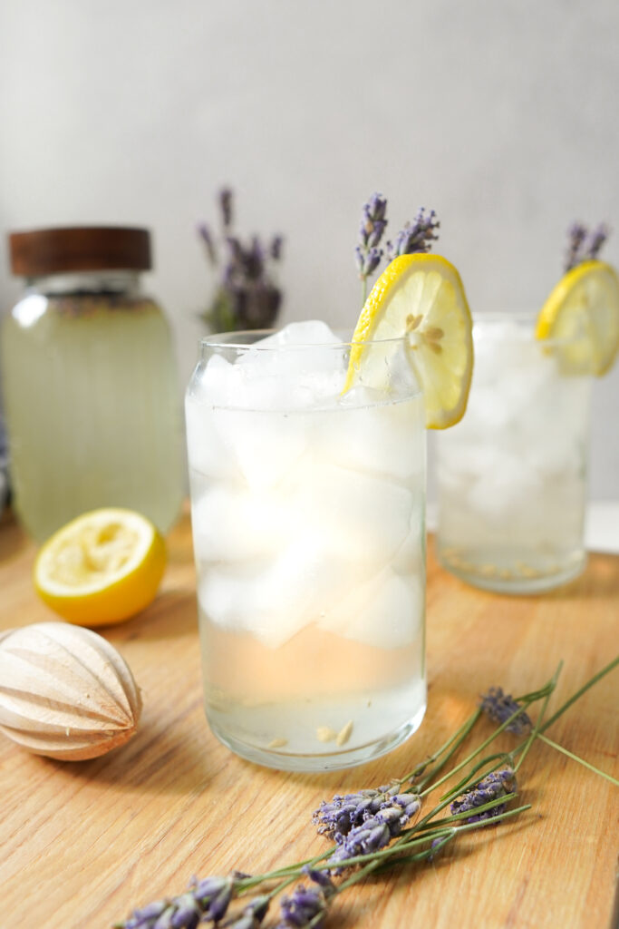 two glasses filled with ice and lavender lemonade with a lemon twist and lavender twig as a garnish