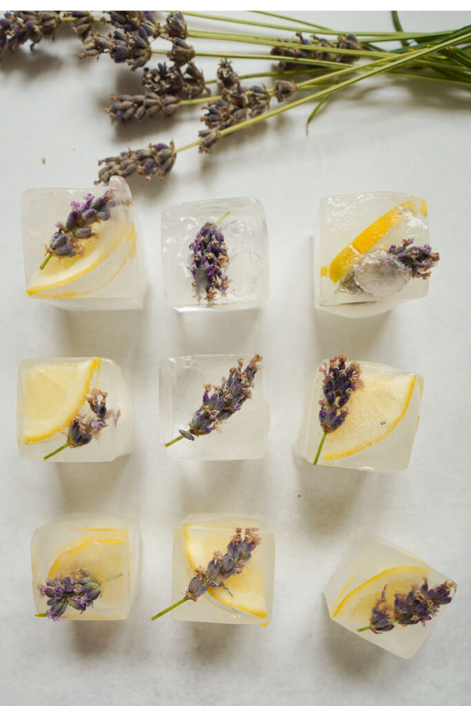 nine square floral ice cubes laying on a table. frozen inside are slices of lemons and lavender.