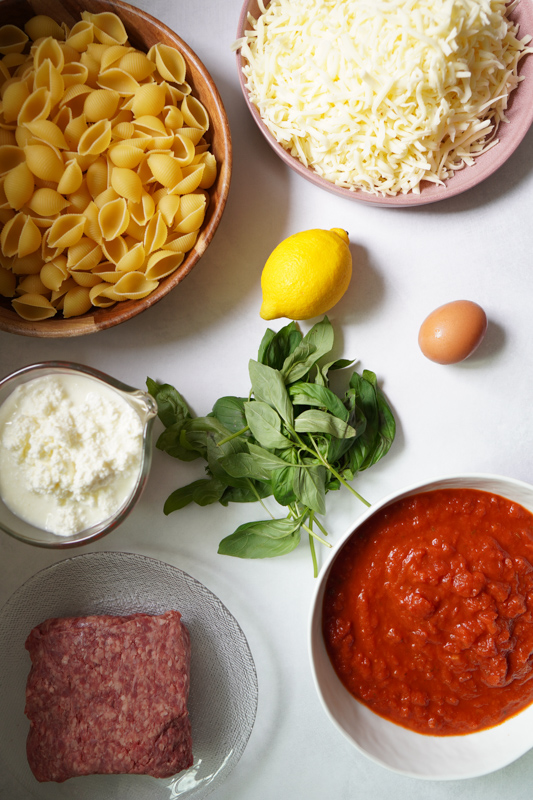 All the ingredients for Lazy Summer Lasagna on a white counter. Shell noodles, fresh mozzarella cheese, lemon, basil, egg, tomato sauce and meat.