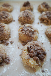 Raw Sour Cream Coffee Cake Cookie Dough scooped, nested, and topped with crumb topping.