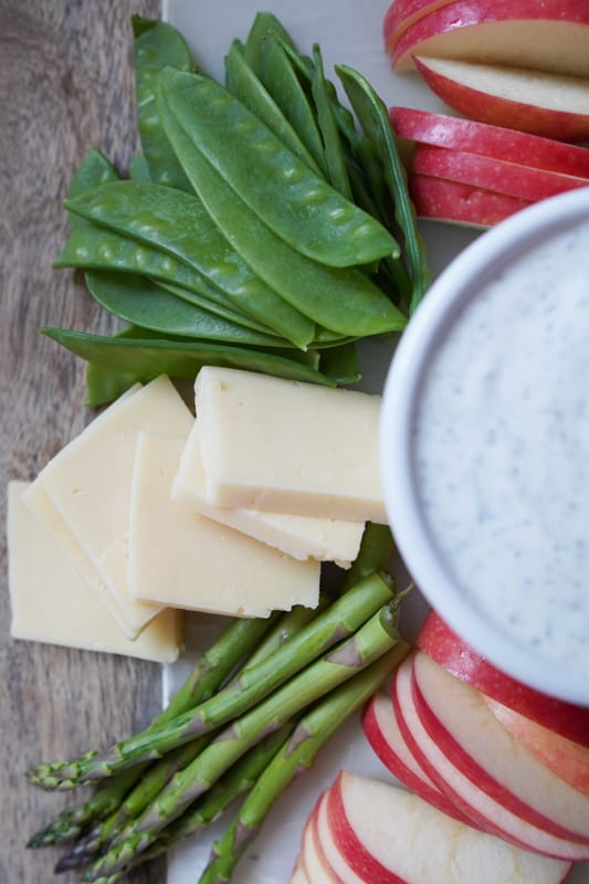 A board with snap peas, cheese, asparagus, and apples surrounding a bowl of greek yogurt ranch dip