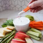 A woman's hand dipping a carrot into a small bowl of Greek Yogurt Ranch Dip